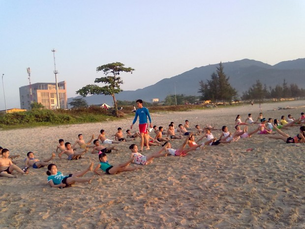 Students warming up at Son Tra beach before hitting the water