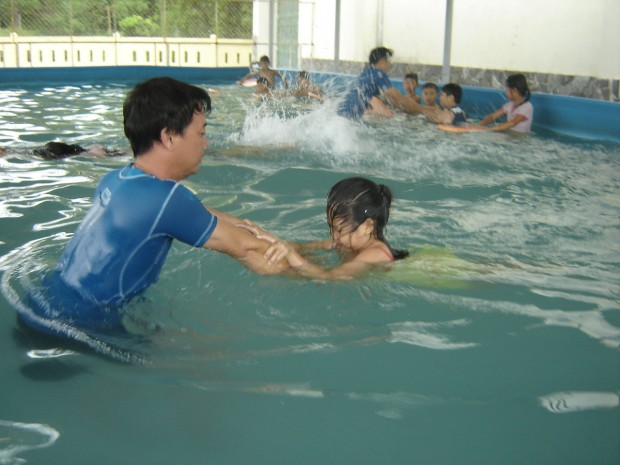 A SwimSafe instructor assists a student who is scared of the water